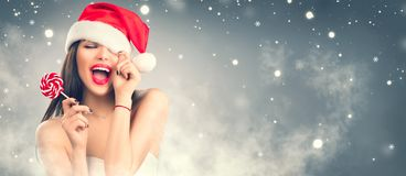 Christmas woman. Joyful model girl in Santa`s hat with red lips and lollipop candy in her hand. Closeup portrait over winter snow background stock photos