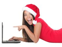 Christmas woman on laptop. Doing internet shopping. Woman excited about buying gifts online or winning something on her laptop computer. Young woman lying down Stock Photos