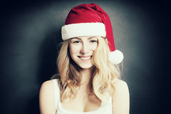 Christmas Woman laugh. Beautiful Xmas Fashion Model in Santa Hat Stock Photo