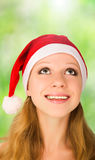 Christmas woman looking up. An attractive young woman in a red Christmas hat royalty free stock photography