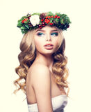 Christmas Woman with Makeup, Blond Curly Hair. And Floral Xmas Wreath. Young Blonde Beauty Royalty Free Stock Images