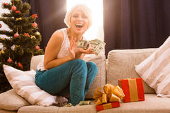 Christmas woman with New Year gift or present. Hppy smiling and laughing Christmas woman holding money dollars given as New Year gift or present by Santa Clause Royalty Free Stock Photo