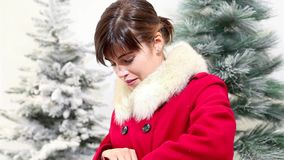 Christmas woman opens bag with gift and surprised smiles, trees in the background stock video