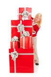 Christmas: Woman Peeking Around Stack Of Fancy Gifts Royalty Free Stock Photos