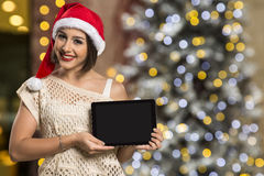 Christmas woman portrait holding tablet. Smiling happy girl over Royalty Free Stock Image