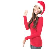 Christmas woman presenting isolated. Santa woman showing copy space standing in red Santa hat. Isolated on white background. Asian Chinese / white Caucasian Stock Photo