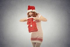 Christmas woman in santa claus red hat holding opening gift bag Stock Photos
