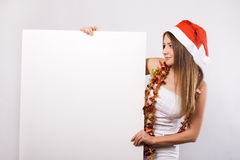 Christmas woman in santa hat with blank billboard Royalty Free Stock Image