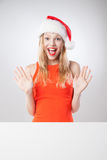 Christmas woman in santa hat holding empty board Royalty Free Stock Photo