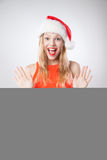 Christmas woman in santa hat holding empty board Stock Photos