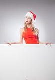 Christmas woman in santa hat holding empty board Royalty Free Stock Photos