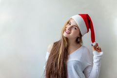 Christmas woman with Santa hat. Santa girl smiling in red Santa hat. Christmas Santa hat  woman portrait . Smiling happy girl on white background Stock Photos