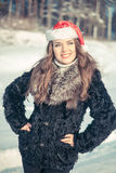 Christmas woman in Santa hat smiling on a background of snowy forest Royalty Free Stock Photos