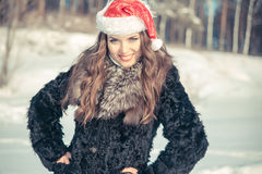 Christmas woman in Santa hat smiling on a background of snowy forest Royalty Free Stock Images