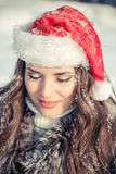 Christmas woman in Santa hat smiling and closed his eyes against the snowy forest Royalty Free Stock Photos