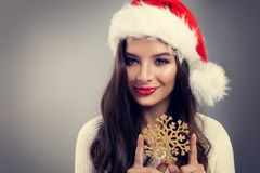 Christmas Woman in Santa Hat Smiling and Holding Winter Snowflake. Fashion Model Girl with Makeup and Long Hair royalty free stock photos