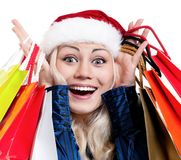 Christmas woman with shopping bags. Portrait of a Christmas woman in santa hat holding a shopping bags over white background Royalty Free Stock Photo