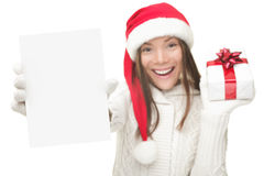 Christmas woman showing copy space sign. Christmas woman showing blank sign with empty copy space. Beautiful young smiling woman in Santa hat holding white paper Royalty Free Stock Images