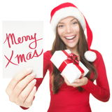 Christmas woman showing copy space sign. Christmas woman showing blank sign with empty copy space. Beautiful young smiling woman in Santa hat holding white paper Royalty Free Stock Photos