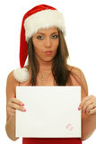 Christmas woman showing copy space sign. Christmas woman showing blank sign with empty copy space. Beautiful young smiling woman in Santa hat holding white paper Royalty Free Stock Photo