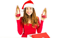 Christmas woman showing her red high heel shoes. Happy christmas woman showing a pair of shoes as her christmas gifts. Isolated on white background stock photos