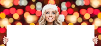 Christmas woman showing white big blank board background stock photo
