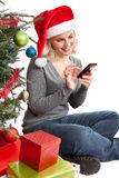 Christmas woman on Smartphone. A woman wearing a santa hat sitting by a Christmas tree and presents touching her Smartphone isolated on white Stock Image