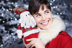 Christmas woman smiling with gift, Santa Claus toy, Royalty Free Stock Photos