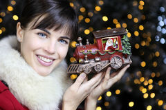 Christmas woman smiling with train toy in lights background Royalty Free Stock Photos