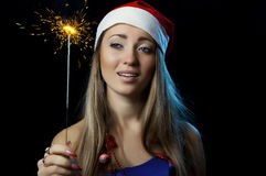 Christmas Woman with sparkler. Smiling Christmas Woman with glowing sparkler Royalty Free Stock Photography