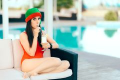 Christmas Woman Spending Holidays Drinking Cocktail by the Pool. Beautiful girl celebrating Xmas in a spa resort Royalty Free Stock Photography