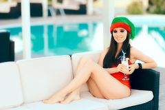 Christmas Woman Spending Holidays Drinking Cocktail by the Pool. Beautiful girl celebrating Xmas in a spa resort Stock Photo