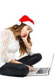 Christmas woman surfing on the internet looking bored. Bored christmas woman  surfing on the internet. Isolated on white background Royalty Free Stock Photography