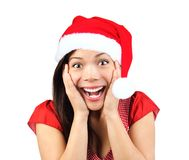 Christmas woman surprised. Christmas girl very excited and surprised holding her head. Beautiful mixed asian / caucasian model. Isolated on seamless white Stock Images