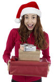Christmas woman surprised by her christmas gifts. Caucasian christmas woman with a Santa Claus hat looking surprised and happy with her christmas gift boxes Royalty Free Stock Images