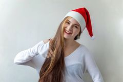 Christmas woman with thumb up. Christmas woman showing thumb up. Santa girl smiling in red Santa hat. Beautiful happy Caucasian woman  on white background Stock Photos