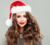 Christmas Woman wearing Santa Hat. Cute Young Woman Model. Christmas Woman wearing Santa Hat. Cute Young Woman Fashion Model with Curly Hair and New Years Party Royalty Free Stock Photography