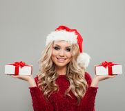 Christmas Woman wearing Santa Hat Showing Two White Xmas Gifts. With Red Silky Ribbon. Smiling Model with Christmas Double Gift Box Royalty Free Stock Photos