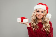 Christmas Woman wearing Santa Hat. Showing White Xmas Gift with Red Silky Ribbon. Smiling Model with Blonde Hair, Makeup and Christmas Gift on Background with Stock Photography