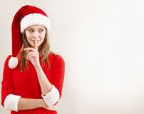 Christmas woman wearing a santa hat whispering christmas secret. Xmas concept. Empty space for greetings and ads Stock Photo