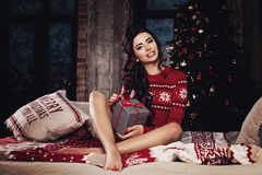 Christmas Woman in Winter Jumper Holding Xmas Gift. Sexy Model Stock Photo