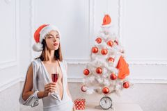 Christmas woman. We wish you a merry christmas. Pretty woman in red Santa Hat on holiday. Happy new year. stock images