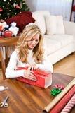 Christmas: Woman Wrapping Christmas Gift. Pretty woman at home, celebrating Christmas Royalty Free Stock Photo