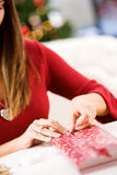 Christmas: Woman Wrapping Small Gift Stock Images