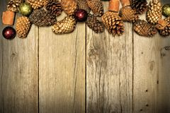 Christmas wood background and pine cone border. Holiday themed wood background with pine cone top border Royalty Free Stock Photo
