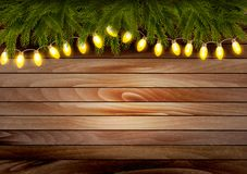 Christmas wooden background with branches and a garland. Royalty Free Stock Image