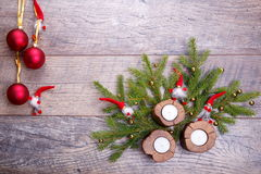 Christmas wooden background with candles and red balls. Christmas gnome decor with santa hat. Holiday bohek background Royalty Free Stock Image
