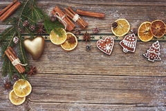 Christmas wooden background with Christmas cookies, heart, cinnamon and Christmas tree. Toned Royalty Free Stock Image