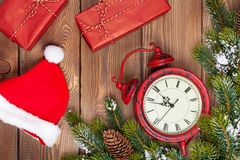 Christmas wooden background with clock, fir tree, gift boxes and Royalty Free Stock Images