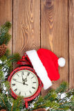 Christmas wooden background with clock, fir tree and santa hat Stock Images